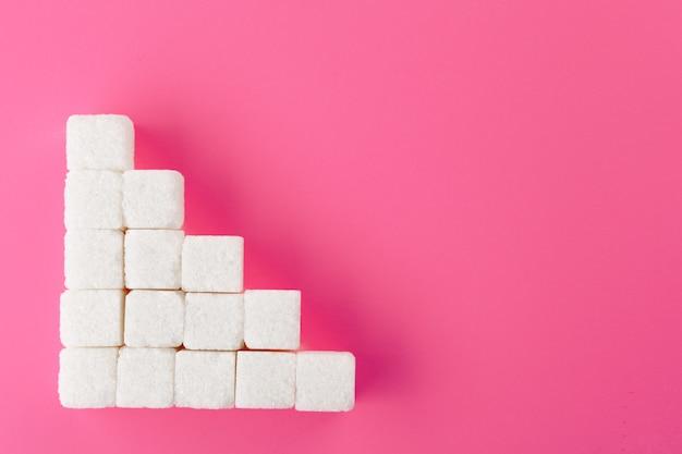 Kubussen van suiker op een roze achtergrond.