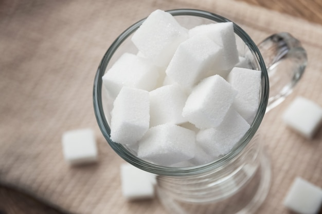 Kubussen van witte suiker in een glazen beker op beige canvas