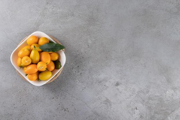 Kumquatvruchten in een kom, op de marmeren tafel.