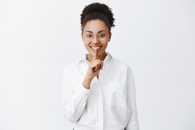 Kun je geheimen bewaren? blije opgewonden afro-amerikaanse vrouwelijke vrouw die stilte gebaar doet