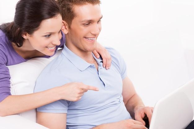 Kun je het geloven! vrolijk jong liefdevol stel zittend op de bank en kijkend naar laptop terwijl vrouw monitor wijst en glimlacht