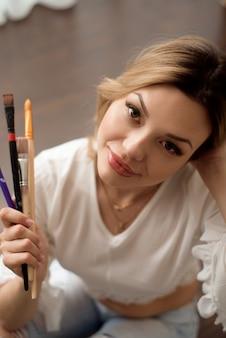 Kunst, creativiteit, werk en creatief beroep concept. vrouwelijke kunstenaar poseren voor raam en schilderen met olie of acrylverf
