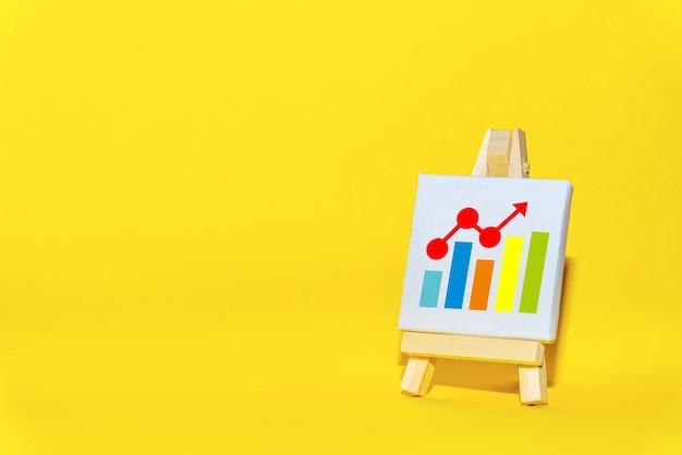 Kunst-ezel op een gele tafel met een positief diagram. concept van succes, groei en prestatieverbetering. statistieken en bedrijfsanalyses, resultatenrekening.