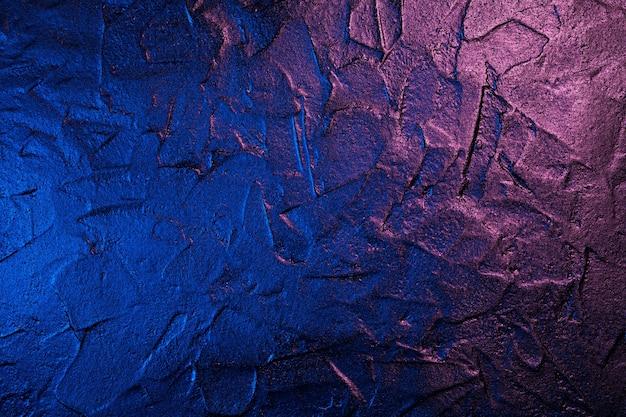 Kunst gepleisterde zwarte muur textuur achtergrond in neon licht