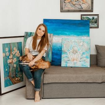 Kunst, het werk van de kunstenaar. de jonge mooie meisjeskunstenaar schildert een beeld. workshop van de kunstenaar. het proces van creativiteit. tekenen en schilderen. inventaris van de kunstenaar. detailopname.