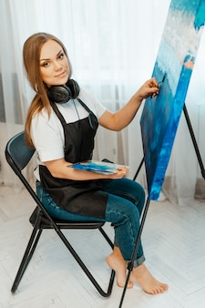 Kunst, het werk van de kunstenaar. jonge mooie meisje kunstenaar schildert een foto en luistert naar muziek met een koptelefoon. workshop van de kunstenaar. tekenen en muziek, verven. inventaris van de kunstenaar. detailopname.