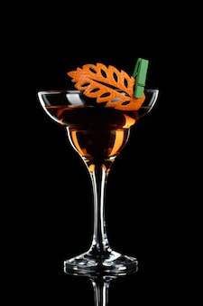 Kunst in het snijwerk van sinaasappelvruchten. hoe maak je een citrus garnituur ontwerp voor een drankje. cocktail rob roy. dranken op basis van whisky.
