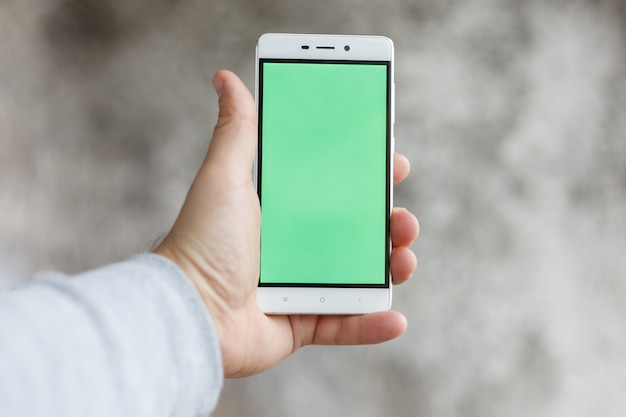 Kunst, mensen, technologieën, 4k en lifestyle concept - close-up man hand vasthouden en aanraken van de telefoon met groen scherm verticaal