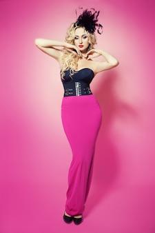 Kunst mode portret van een jonge mooie elegante blonde vrouw met massieve sprankelende oorbellen, mode zwarte hoed met veren, make-up en kapsel poseren in korset en lange strakke roze rok