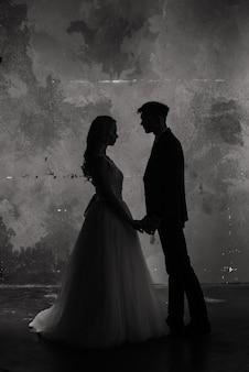 Kunst mode studio foto van bruidspaar silhouet bruidegom en bruid op kleuren achtergrond.