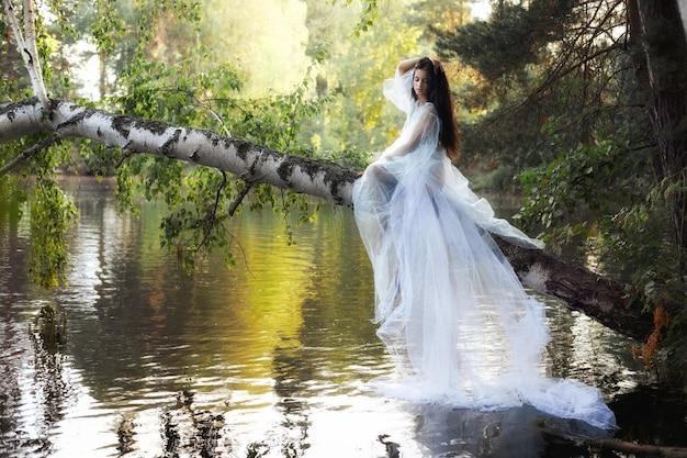 Kunst mooie romantische vrouw in blauwe lange jurk zittend op omgevallen boom boven rivier. donkerbruine vrouw in transparante jurk