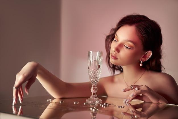 Kunst mooie vrouw met creatieve make-up ligt op de spiegel.