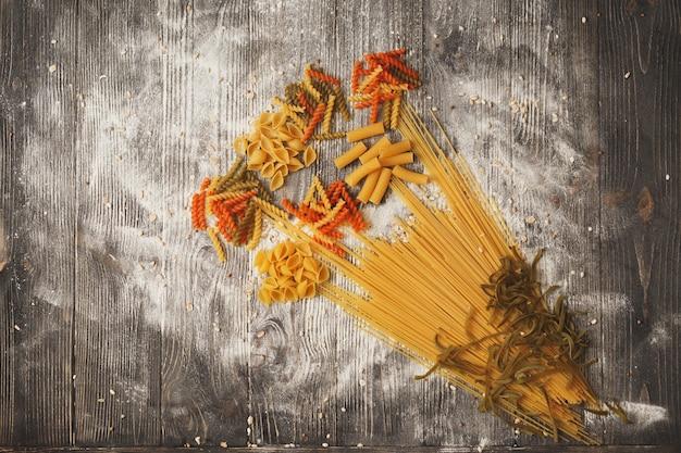 Kunst samenstelling van boeket bloemen gemaakt van verschillende soorten pasta op een zwarte houten achtergrond. bovenaanzicht