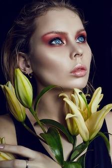 Kunst schoonheid meisje gezicht close-up met lelies in handen