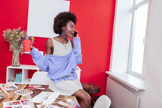 Kunst student. slimme creatieve kunststudent die telefonisch met haar vriend spreekt terwijl ze koffie drinkt