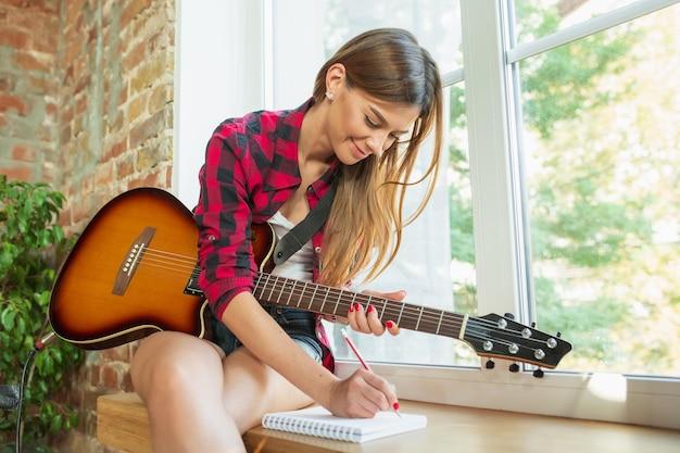 Kunst. thuismuziekstudio, mooie vrouw die muziek opneemt, zingt en gitaar speelt terwijl ze op de loft-werkplek of thuis zit. concept van hobby, muziek, kunst en creatie. eerste single maken.