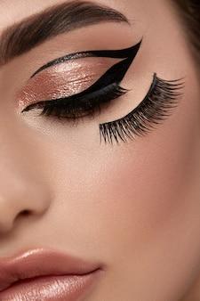 Kunst van make-up artist met valse wimpers en zwarte eyeliner