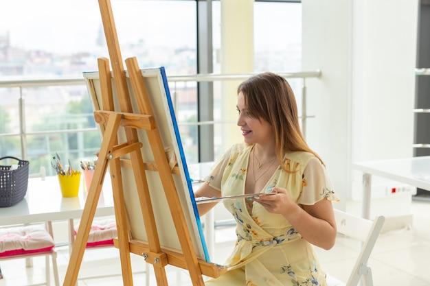 Kunstacademie, creativiteit en vrije tijdsconcept - studentenmeisje of jonge vrouwenkunstenaar met schildersezel, palet en verfborstel die beeld schilderen bij studio