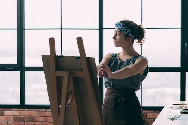 Kunstacademie. jonge dame die leert schilderen, met behulp van ezel