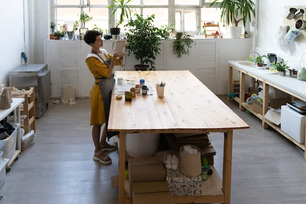 Kunstatelier voor cursussen keramiek maken van aardewerk met jonge vrouwelijke ambachtsvrouw houd pottenbakkerskruik vast