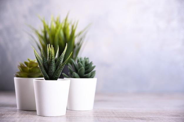 Kunstbloemen gras andere vorm in een pot op houten achtergrond close-up met kopie ruimte en tekst.