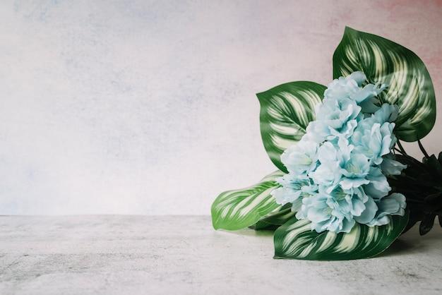Kunstbloemen met bladeren op witte geweven achtergrond