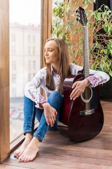 Kunstenaar die binnen gitaar houdt en door de vensters kijkt