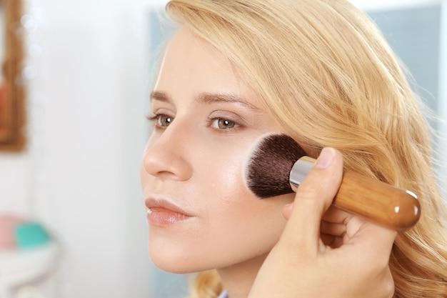 Kunstenaar die blos met make-upborstel toepast