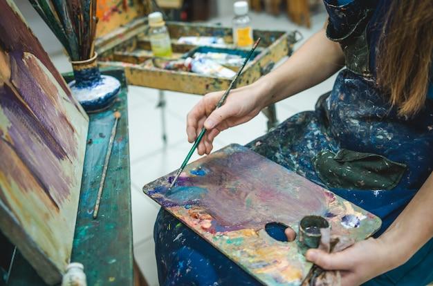 Kunstenaar die een beeld in een studio schildert. close-up bekijken