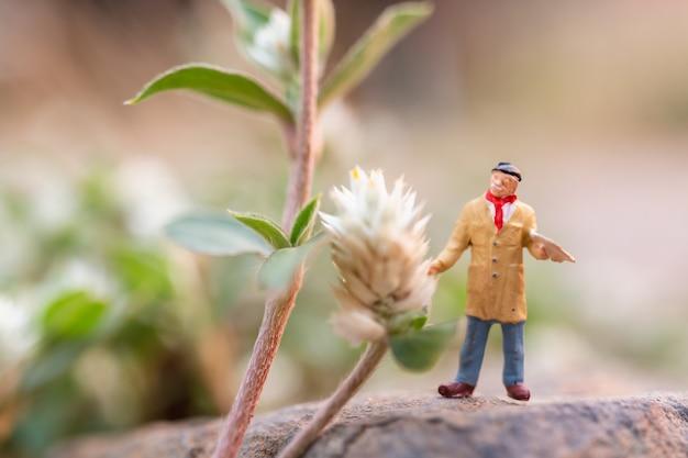Kunstenaar die een borstel houdt en bloem in de tuin schildert