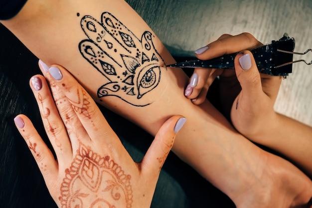 Kunstenaar die henna mehndi-tatoeage op vrouwelijke hand toepast
