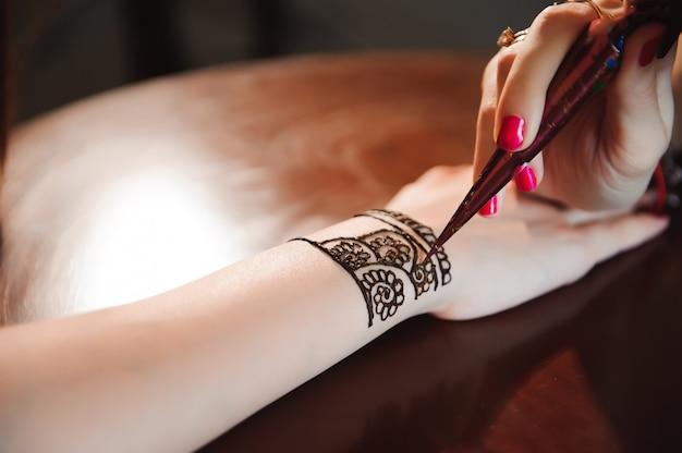 Kunstenaar die hennatatoegering op vrouwenhanden toepast. mehndi is traditionele indiase decoratieve kunst.