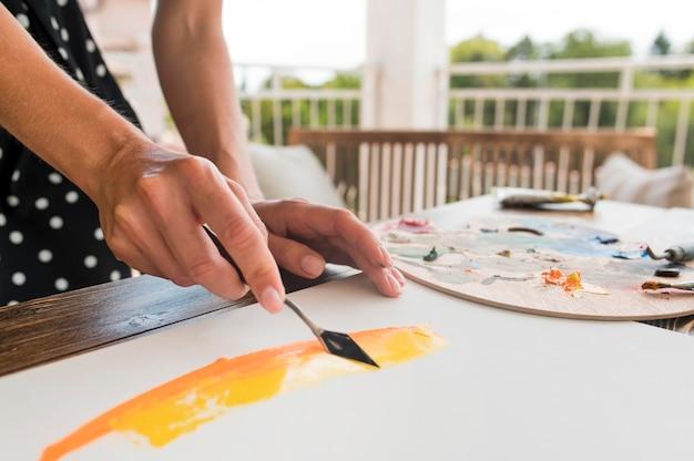 Kunstenaar die hulpmiddel gebruikt om te schilderen