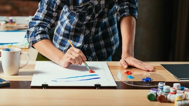Kunstenaar die in zijn atelierwerkruimte schildert