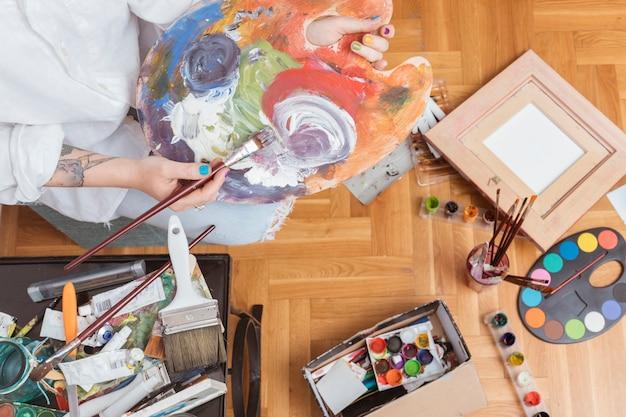 Kunstenaar die kleurstof op palet mengt
