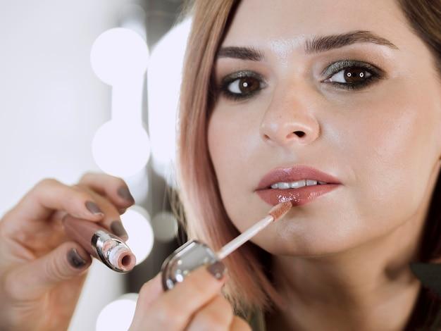 Kunstenaar die lipgloss op model toepast