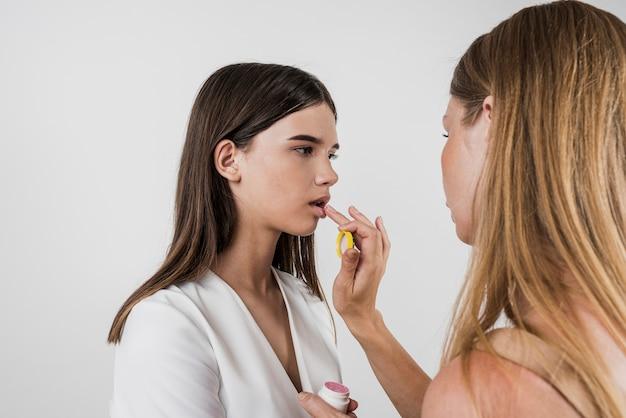 Kunstenaar die lippenbalsem op model toepast
