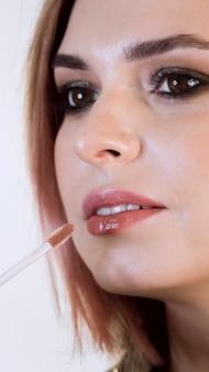 Kunstenaar die lippenstift op mooie vrouw toepast