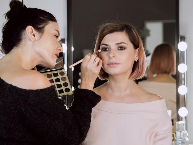 Kunstenaar die make-up op leuk model toepast