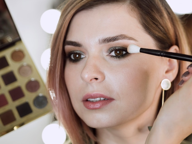 Kunstenaar die make-up op mooie vrouw toepast