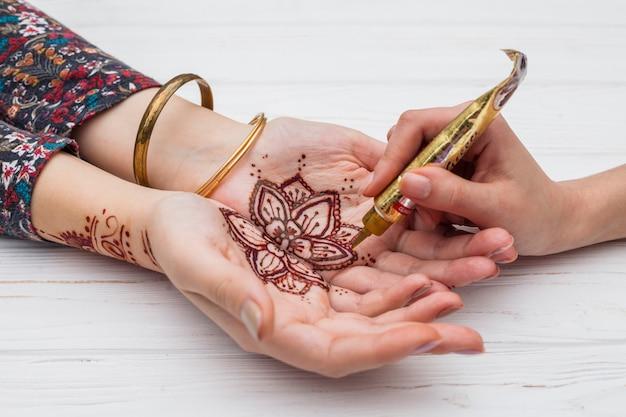 Kunstenaar die mehndi op de palmen van de vrouw maakt