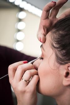 Kunstenaar die oogschaduw met borstel toepast