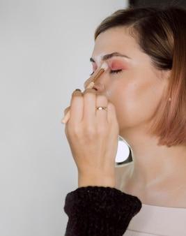 Kunstenaar die oogschaduw op model toepast