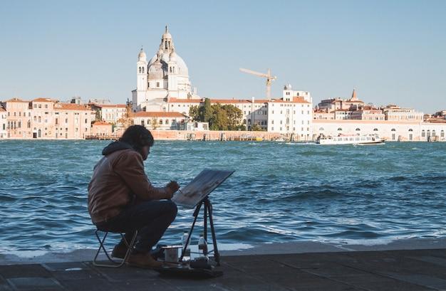 Kunstenaar die overdag de grachten van venetië in italië schildert