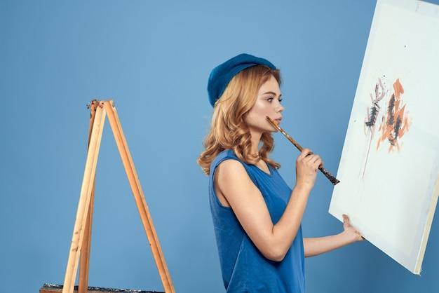 Kunstenaar die penseel houdt en naar illustraties kijkt