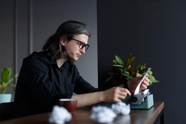 Kunstenaar die thuis een brief typt