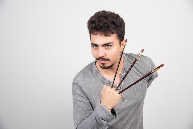Kunstenaar die zijn nieuwe set professionele schilderborstels vasthoudt.