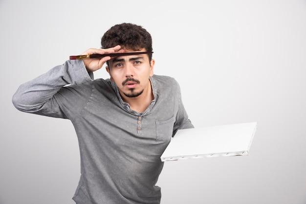 Kunstenaar die zijn penseel tegen zijn hoofd zet en nadenkt over creatieve ideeën.