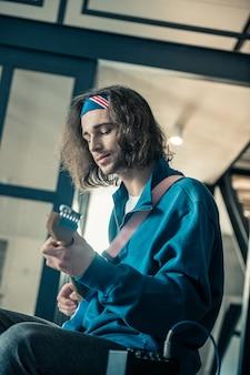 Kunstenaar experimenteren. vreedzame knappe jongeman in bandana die zich concentreert op de mogelijkheden van zijn instrument terwijl hij persoonlijke herhaling heeft