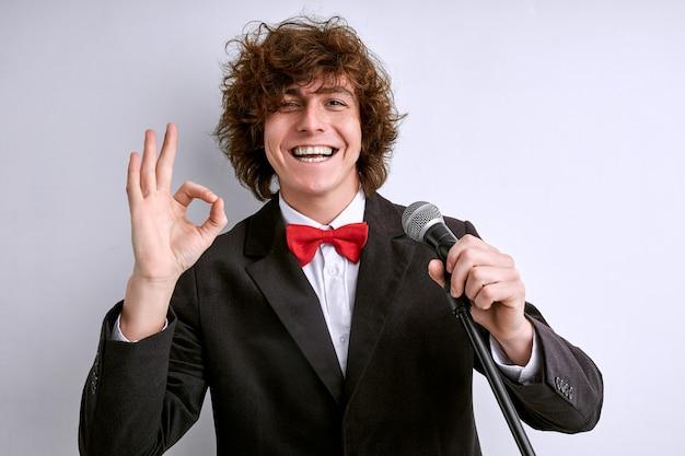 Kunstenaar in pak met microfoon die ok gebaar toont en lacht, de presentatie of toespraak is een goede, succesvolle uitvoering